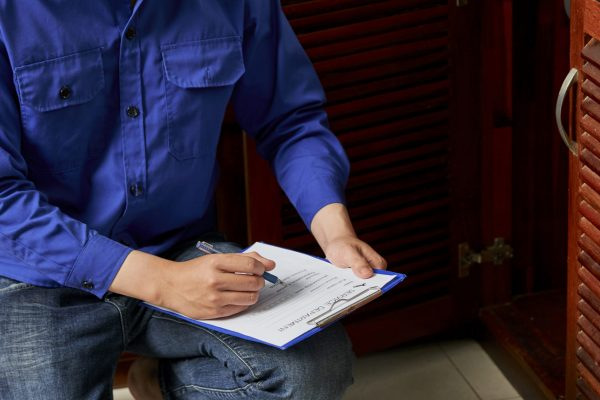 Young plumber in uniform notes his work in document while sitting in the kitchen in apartment